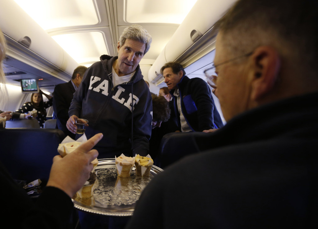 U.S. Secretary of State John Kerry offers cupcakes to members of the travelling press between Washington and the Middle East